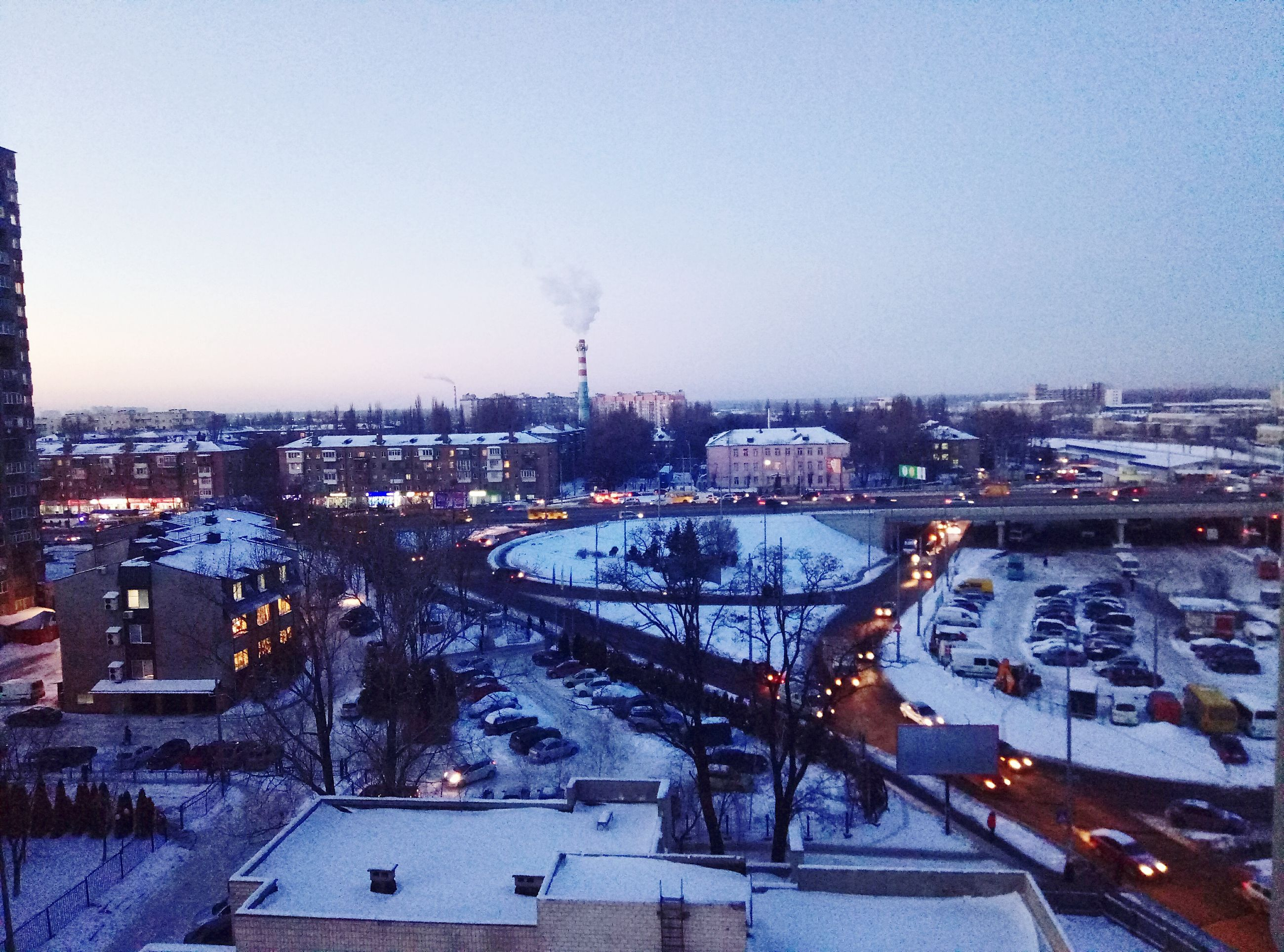 transportation, city, high angle view, architecture, sky, building exterior, travel destinations, built structure, cityscape, winter, illuminated, outdoors, snow, tower, nature, traffic circle, rush hour, no people, snowing, day