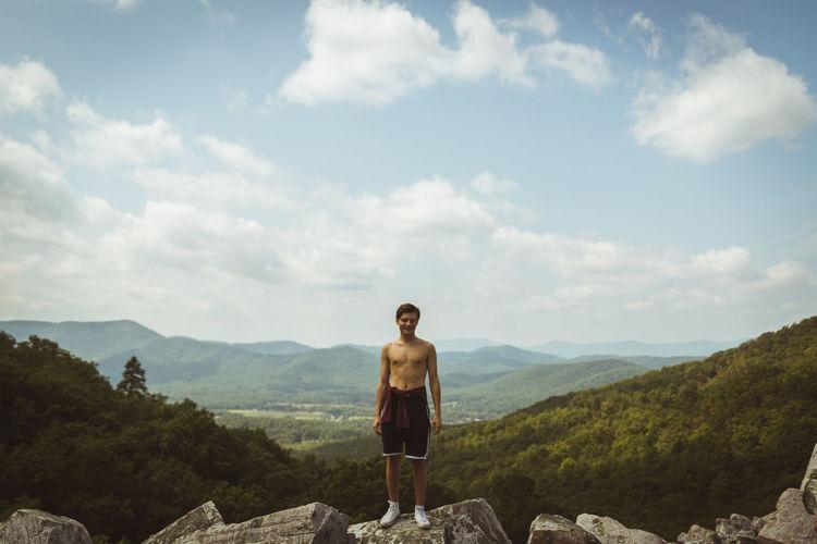 Full length of shirtless man standing on rock against sky