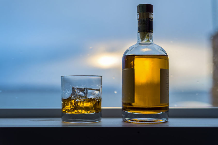 Expensive bottle of amber alcohol with ice on window sill. Alcohol Amber Bottle Bourbon Dram Drinking Entertaining Expensive Glass House Ice Lake Lifestyle Liquid Liquor Malt Masculine Rocks Scotch Sea Success Vibrant Color Wealth Whiskey Window