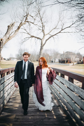 Stylish couple holding hands walking in country on bridge Young Adult Two People Heterosexual Couple Stylish Fashion Positive Emotion Outdoors Couple - Relationship Bonding Bare Tree Lifestyles Front View Women Full Length Real People Love Togetherness Redhead Dress Businessman Nebraska Bridge Walking In The Woods Holding Hands Happiness Beautiful People Beautiful Woman Potrait Moments Of Happiness