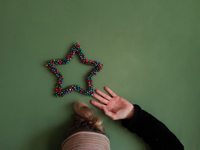Woman Gesturing On Star Shape Over Wall