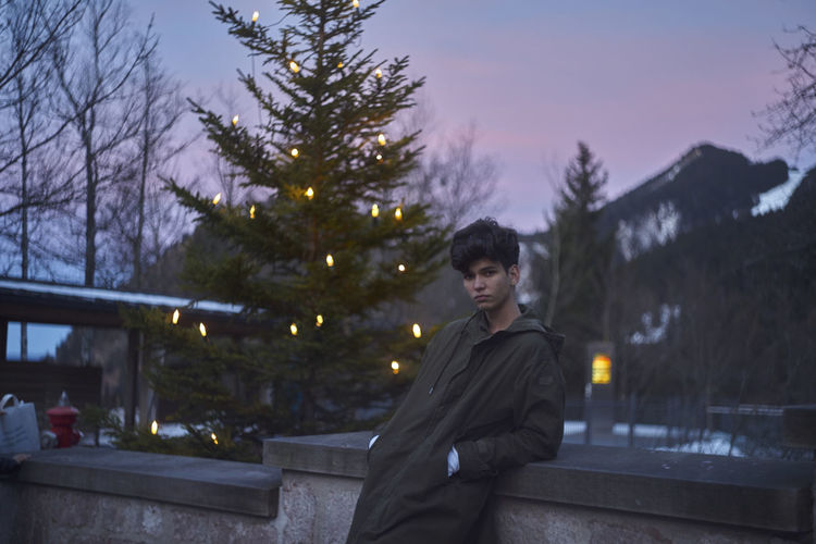 Man against christmas tree during sunset