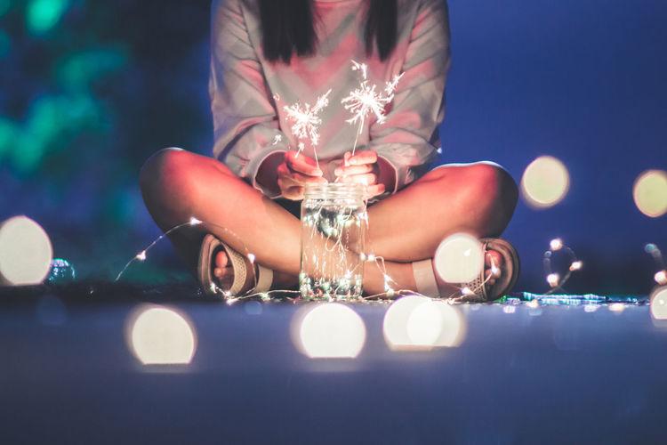 Close-up of handshuman leg holding illuminated lighting equipment at night