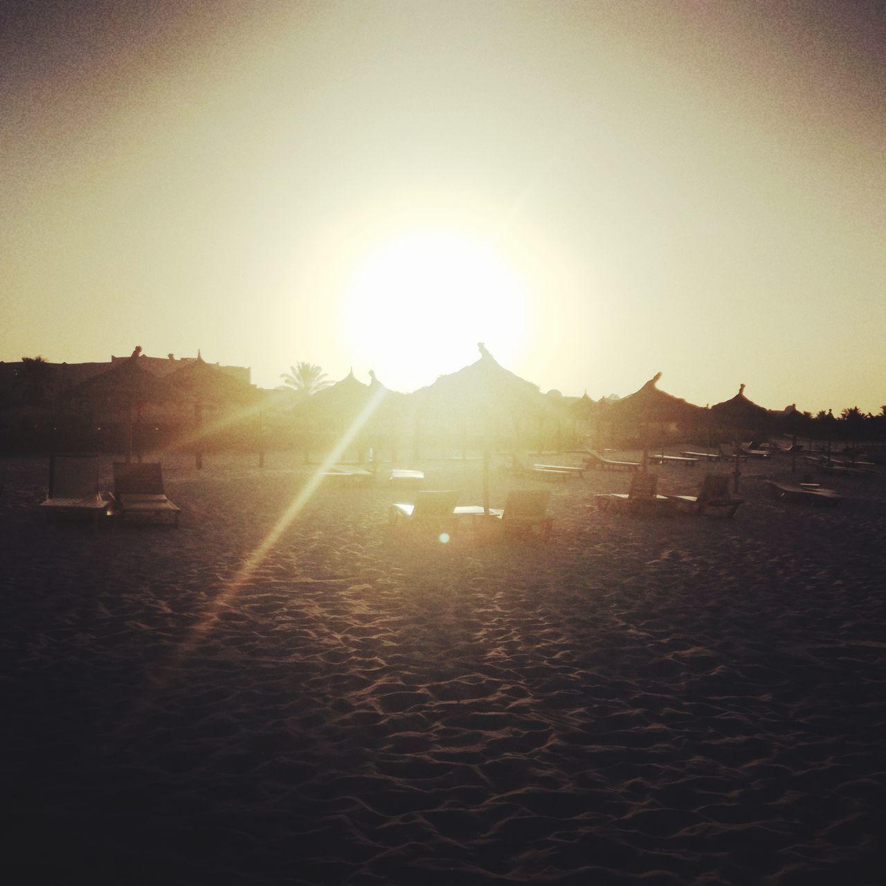 SCENIC VIEW OF BEACH AGAINST BRIGHT SUN