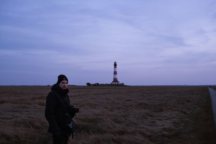 Young woman standing on field by lighthouse against sky