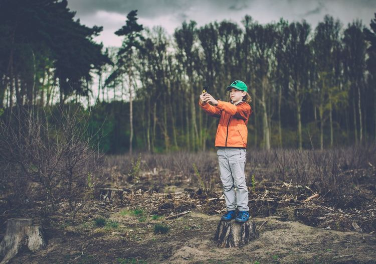 Full length of boy taking selfie through mobile phone while standing at forest