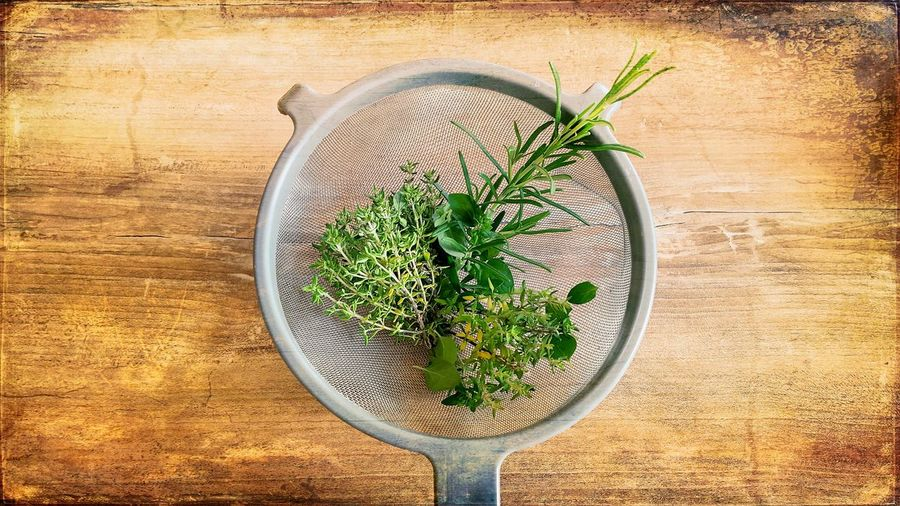 Directly above shot of herbs in tea strainer on table