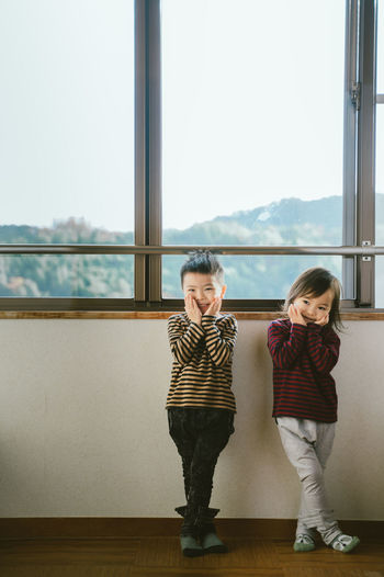 Full length of cute siblings standing with head in hands against window