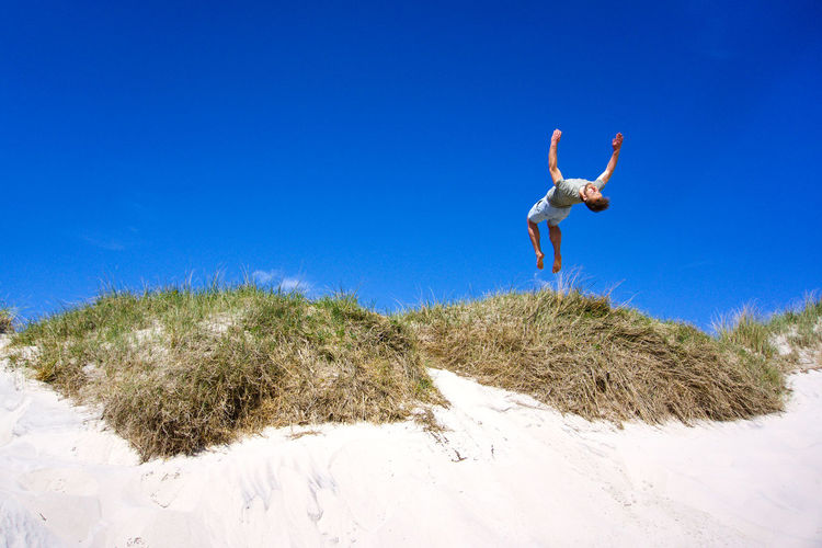 Low angle view of young woman jumping on beach against clear blue sky