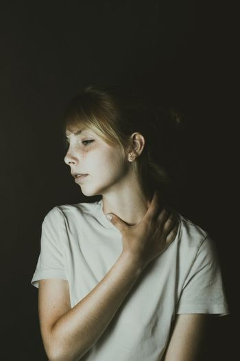 Young Woman Touching Neck Over Black Background