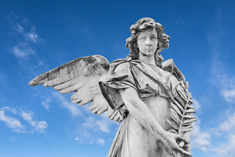 Statue of an angel with olive branches with sky and clouds in the background God Ancient Angel Angelic Antique Art Background Beautiful Catholic Cemetery Christian Death Easter Faith Female Funeral Grave Graveyard Guardian Heaven Holy Marble Monument Old Peace Peaceful Pray Prayer Religion Religious  Sad Sadness Sculpture Sorrow Statue Stone Symbol White Winged Wings Sky Clouds