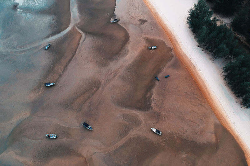 High angle view of boats moored on sand at beach
