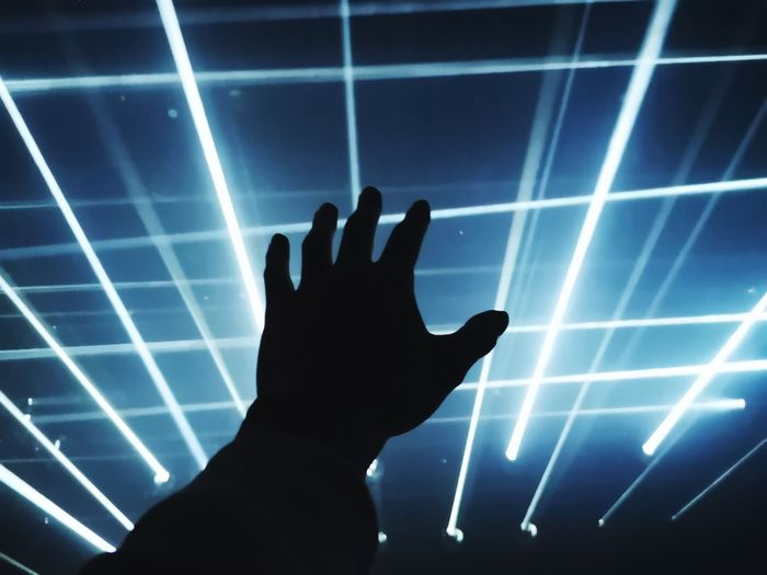 Silhouette of person touching illuminated light