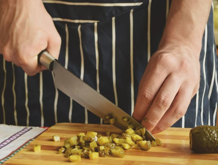 Midsection Of Chef Cutting Pickled Cucumber With Knife On Table