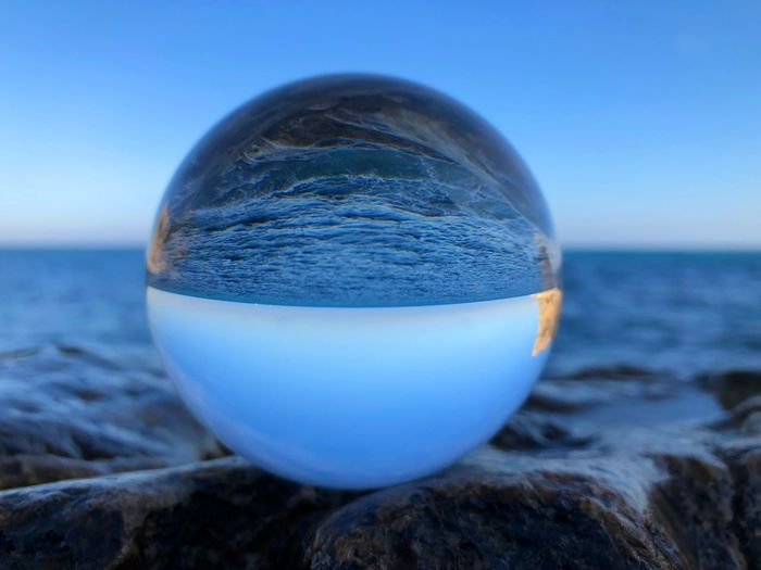 Close-up of crystal ball on rock at sea shore against blue sky