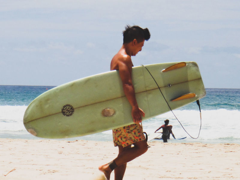 young surfer walking at the beach Beach Day Horizon Over Water Leisure Activity Lifestyles Men Nature One Person Outdoors Real People Sand Scenics Sea Shore Sky Sport Summertime Surfboard Surfer Vacations Walking Water Weekend Activities Young Adult