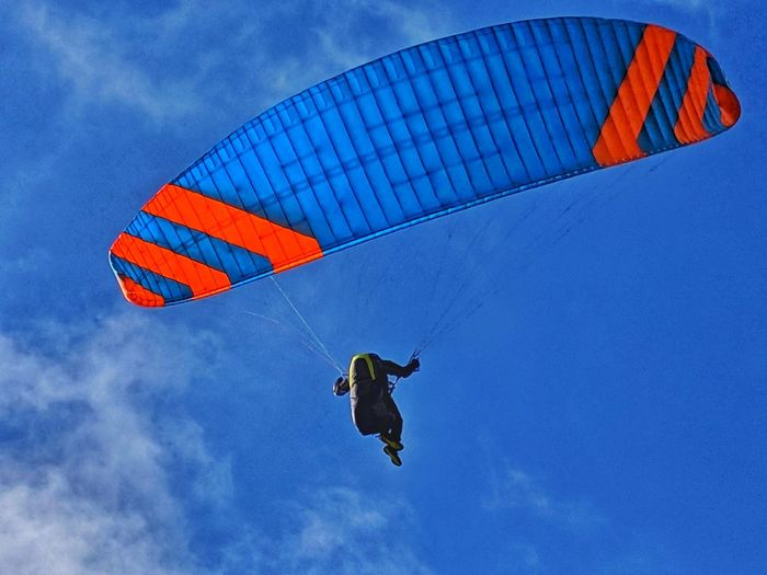 Paraglider. Extreme Sport. Exhilarating. Paragliding. Red Paragliding Paraglider Blue Clouds Man Windy Therapeutic Zen Exhilarating Thrill Sjy Overhead Sport Paragliding Parachute Extreme Sports Flying Adventure Full Length Sport Mid-air Skydiving Blue Gliding