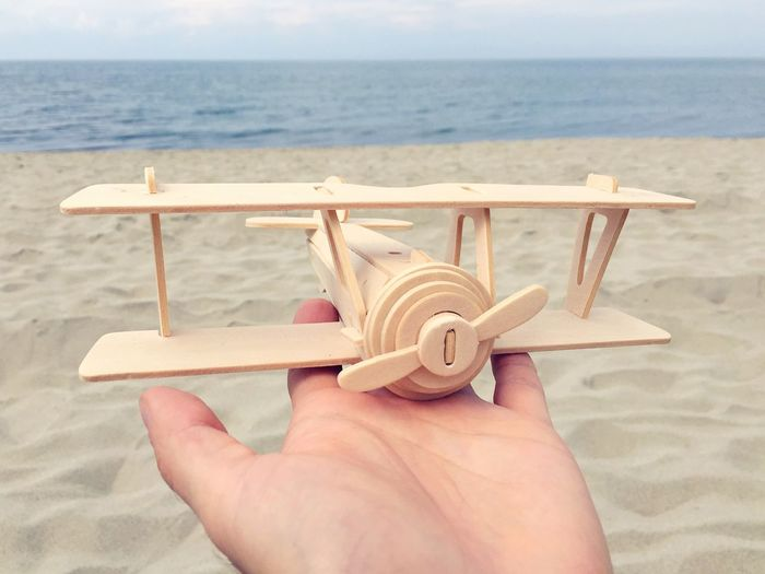 Wooden Toy Toy On The Palm Of The Hand Airplane Plane Seaside At The Sea At The Beach EyeEm Best Shots Beach Sea Hand Wooden Toy Sand Childhood Dreaming Showing Baltic Sea Air Airplane Shot Focus Object