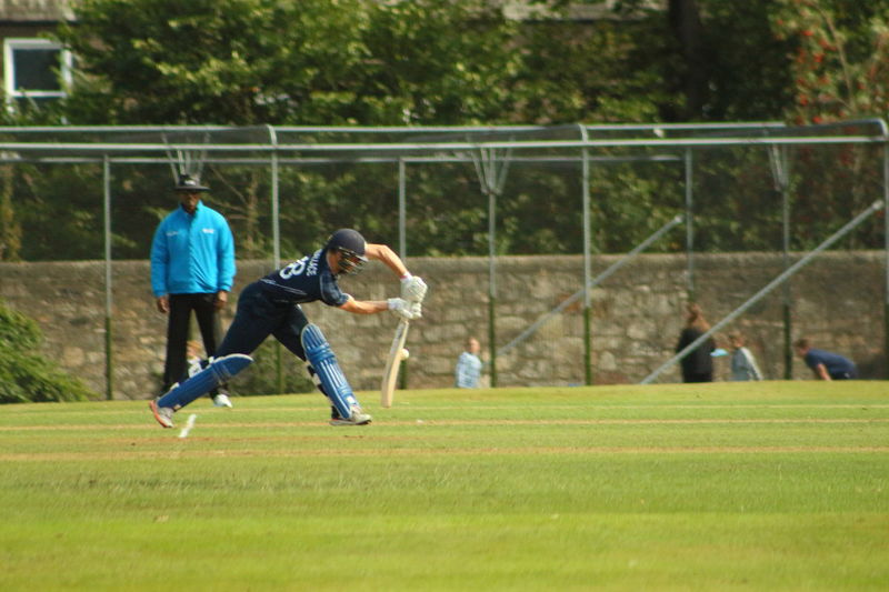 Competition Competitive Sport Cricket Day Edinburgh Effort Enjoyment Focus On Foreground Full Length Grass Green Color HongKong Leisure Activity Lifestyles Motion Net - Sports Equipment Outdoors Playing Scotland Sport Sportsman Team Sport Teamwork The Color Of Sport