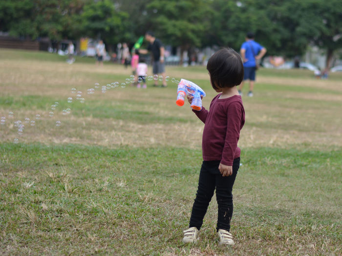 Child Childhood Children Children Only Children Playing Day Full Length Grass Green Park Leisure Activity One Person Outdoors Park Life People Real People Soap Bubble Gun Soap Bubbles Standing Park Life Small Child Childsplay Taiwanese Taiwan Taiwanese Child child playing Boys And Girls