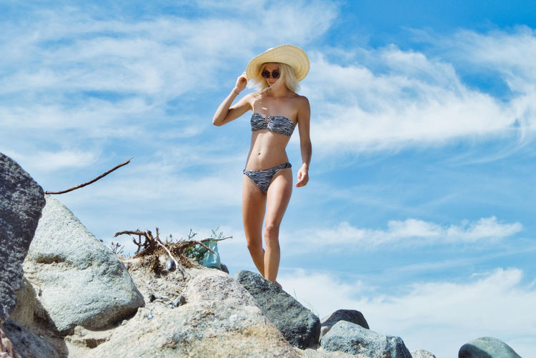 Woman in bikini with hat standing on rock at beach against sky
