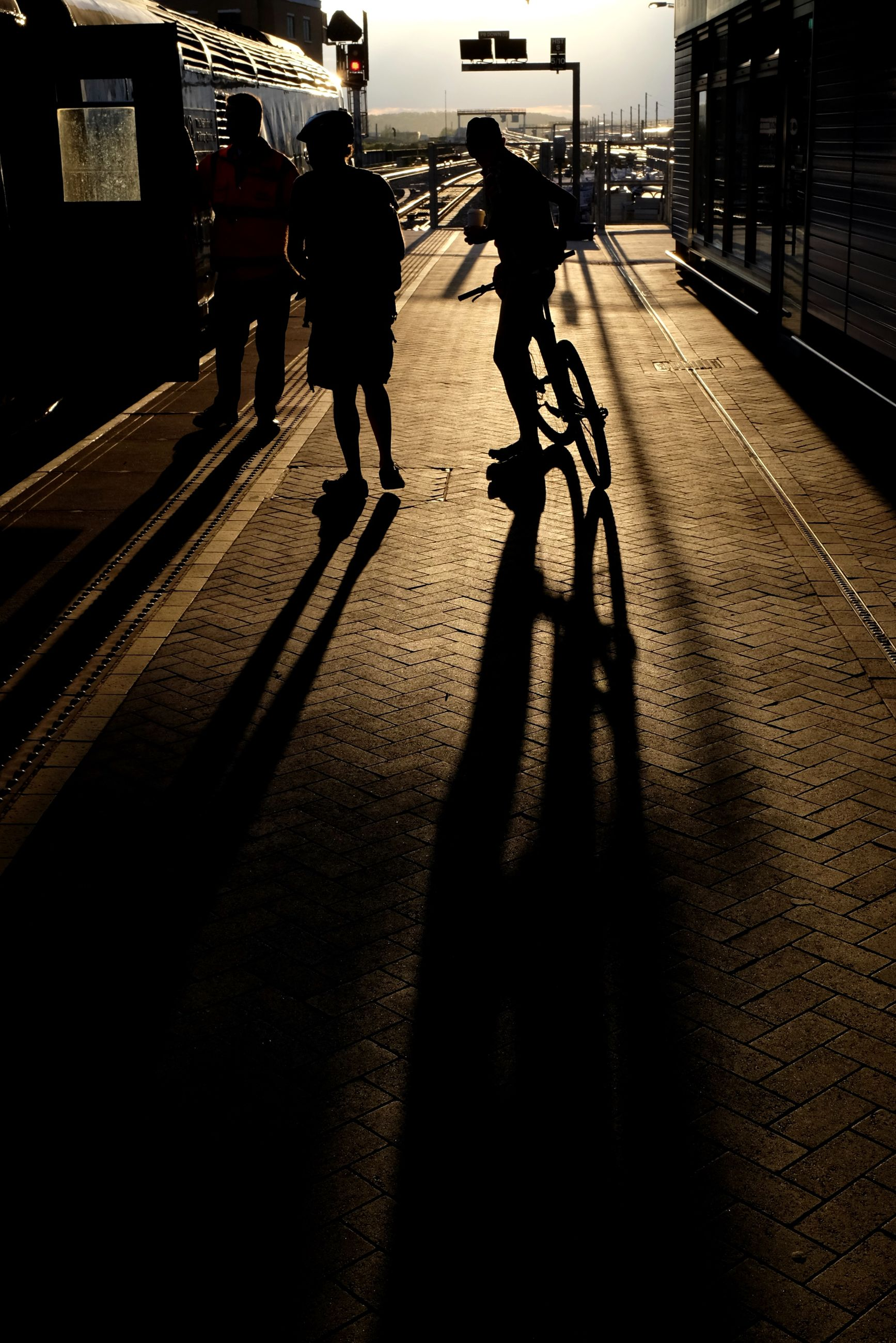 street, walking, men, lifestyles, city life, city, shadow, person, transportation, full length, road, city street, building exterior, sunlight, leisure activity, zebra crossing, road marking, built structure, on the move