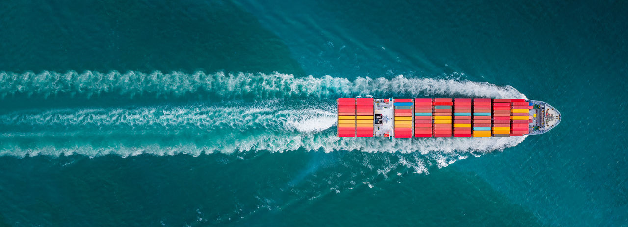 Aerial top view of cargo ship with contrail in the ocean sea ship carrying container