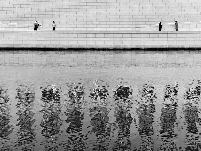People walking by swimming pool in lake
