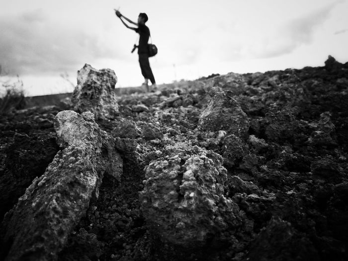 Low Angle View Of Man Standing On Rock Formation