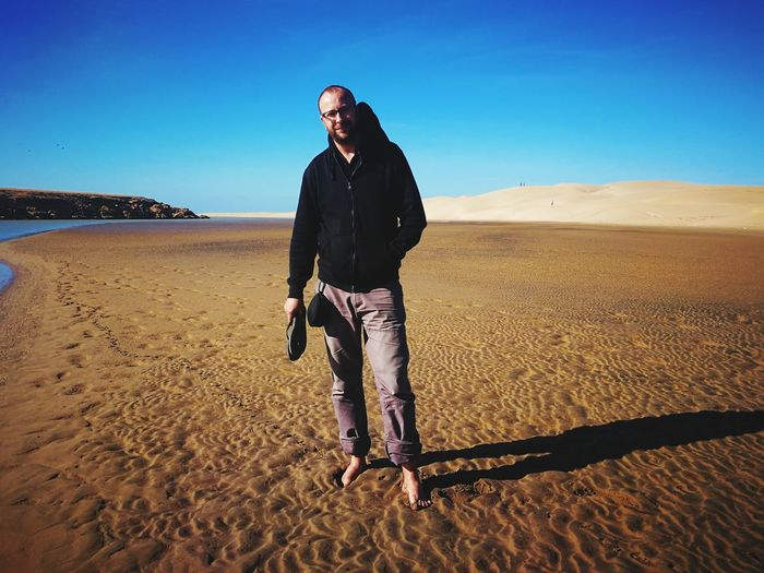 Full length of man standing on sand at beach against clear sky