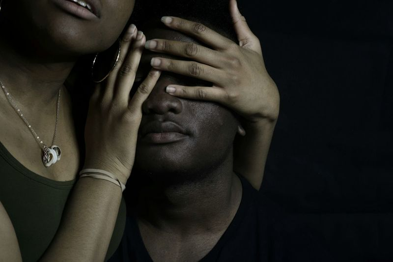 Woman covering eyes of man against black background