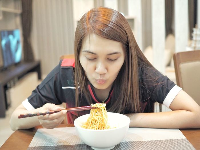 Woman having noodles at home