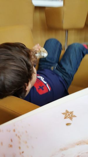 Close-up of boy sitting on table at home