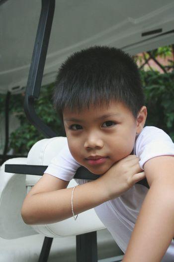Portrait of cute boy sitting in play equipment
