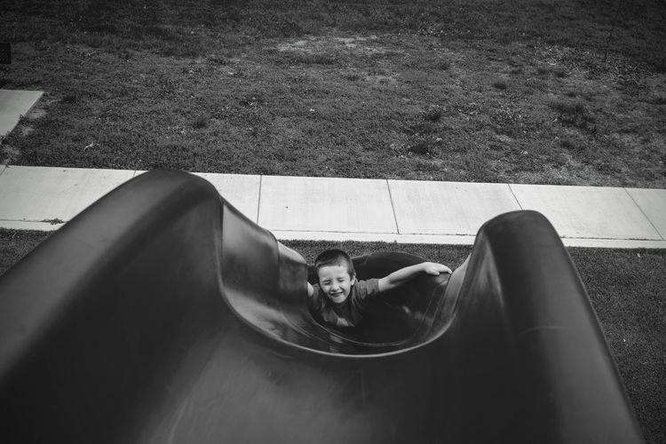 High Angle View Boy Playing At Slide