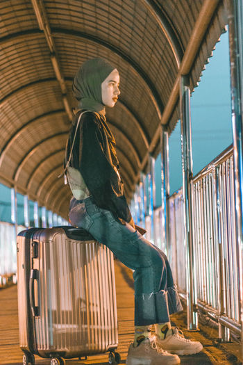 Side view of girl sitting on suitcase by railing