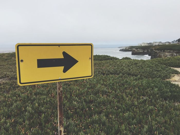 Directional Sign At Beach Against Sky