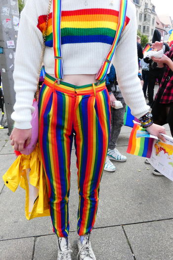 Low Section Of Woman In Rainbow Clothing Standing On Footpath