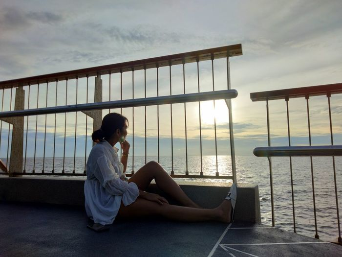 Side view of woman sitting on railing against sky