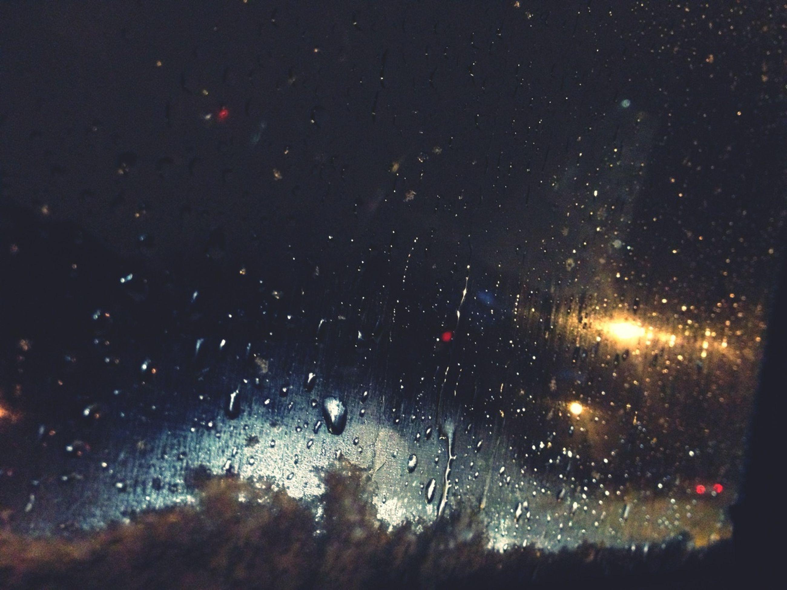 window, wet, night, drop, rain, transparent, glass - material, car, season, transportation, indoors, weather, land vehicle, windshield, vehicle interior, illuminated, raindrop, mode of transport, full frame, water