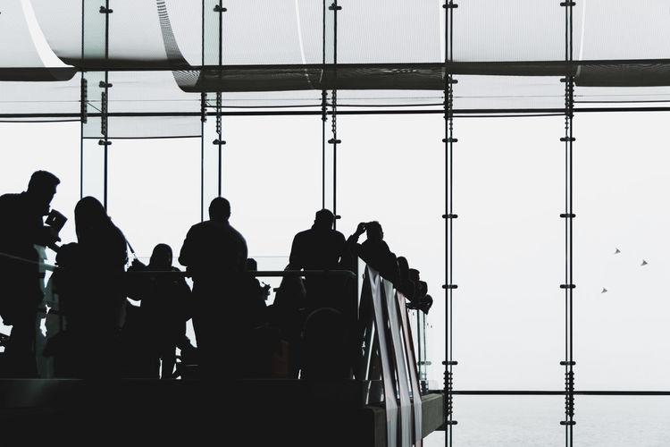 People standing on airport runway against clear sky