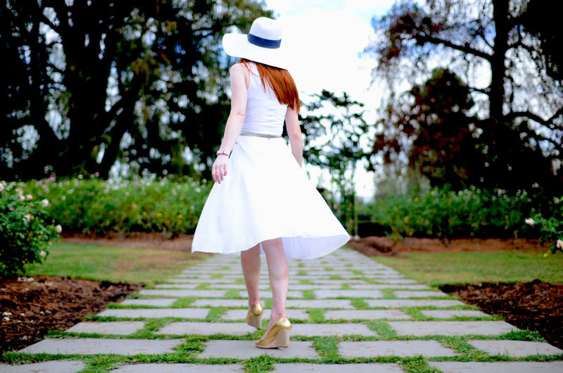 Rear view of woman walking on footpath at public park