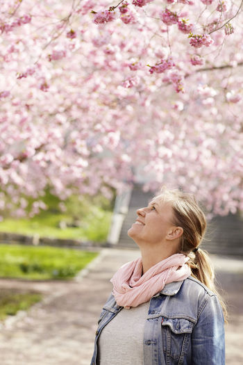 Close-up of young woman with pink cherry blossom outdoors