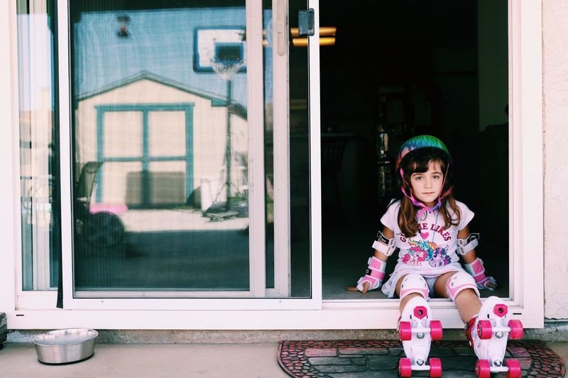 Full length of girl wearing roller skate while sitting in doorway