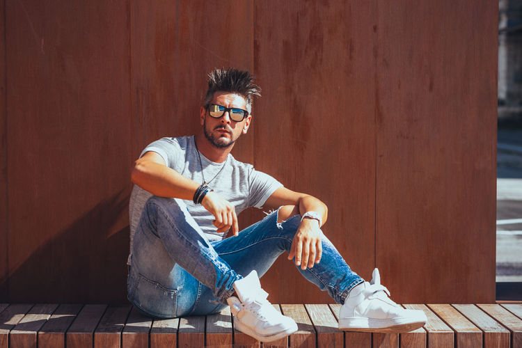 Sitting Casual Clothing One Person Young Adult Glasses Full Length Leisure Activity Young Men Real People Lifestyles Front View Smiling Fashion Wood - Material Portrait Relaxation Looking At Camera Day Outdoors Jeans