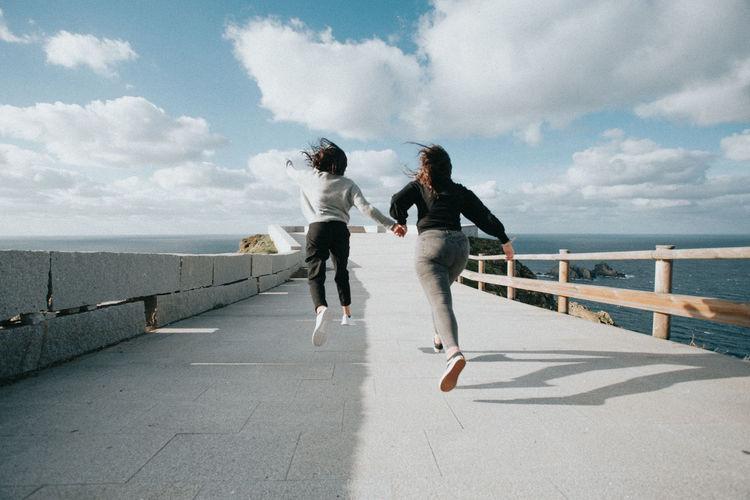 Rear view of women running against sky