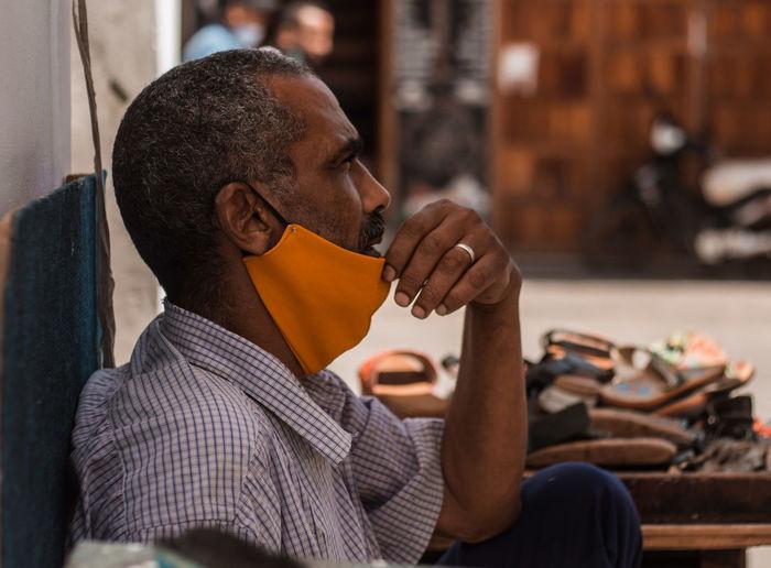 Thoughtful cobbler wearing mask sitting on street