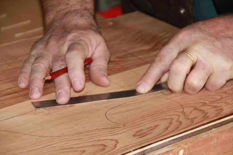 Close-Up Midsection Of Carpenter Measuring Wood At Workshop