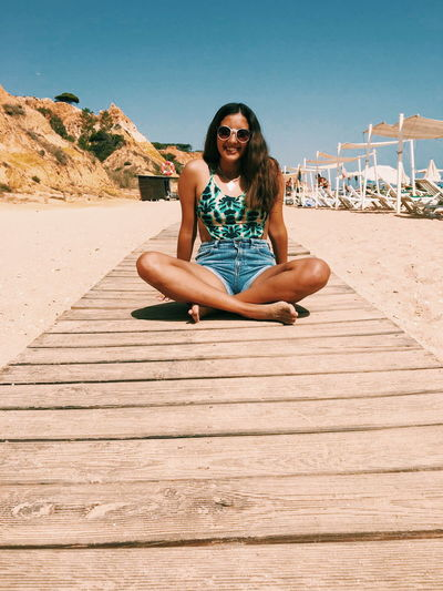 EyeEm Selects Sitting Sand Adult Only Women Adults Only Young Adult One Person Long Hair People Sunny One Woman Only Portrait Young Women Summer Outdoors Full Length Looking At Camera Vacations Fun Happiness Been There.