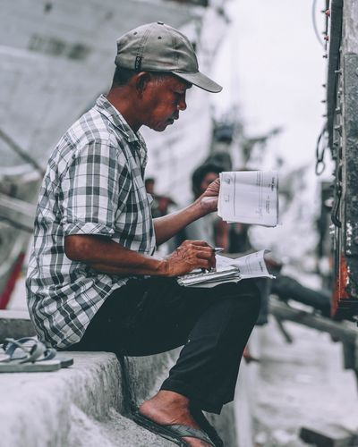Side view of man working while sitting on footpath